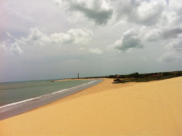 Praia de Caiçara do Norte, com o Farol de Santo Alberto bem na ponta - www.viajandocomaman.com.br - Foto: Amandina Morbeck.