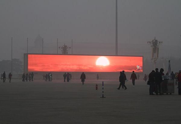 Em Pequim, painéis como esse mostram o nascer do sol, pois o verdadeiro não pode ser visto por causa da poluição - China lança seguro antipoluição do ar para turistas - Foto: Reprodução/Daily Mail.